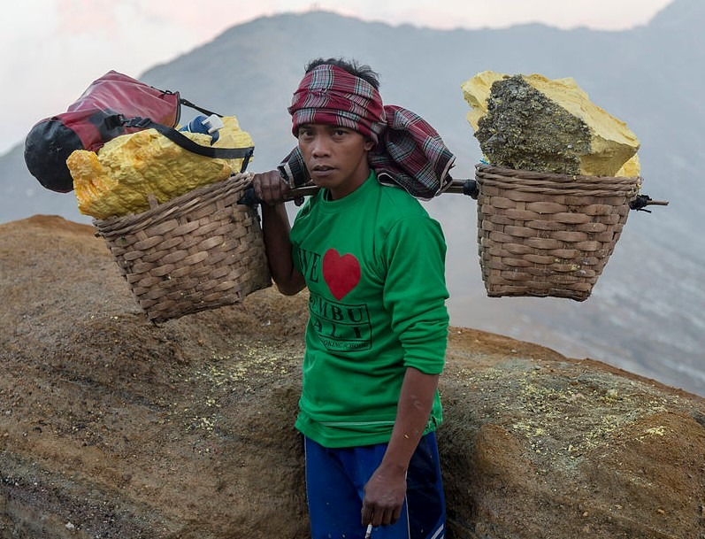 a middle-aged sulfur miner carrying a basket-like container with 90 kg of sulfur carried from the floor of the Ijen Volcano
