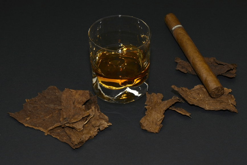 A glass of alcohol , cigar and tobacco leaves scattered around